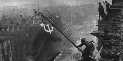 Two soldiers raise the USSR flag above the smoky skies of Berlin