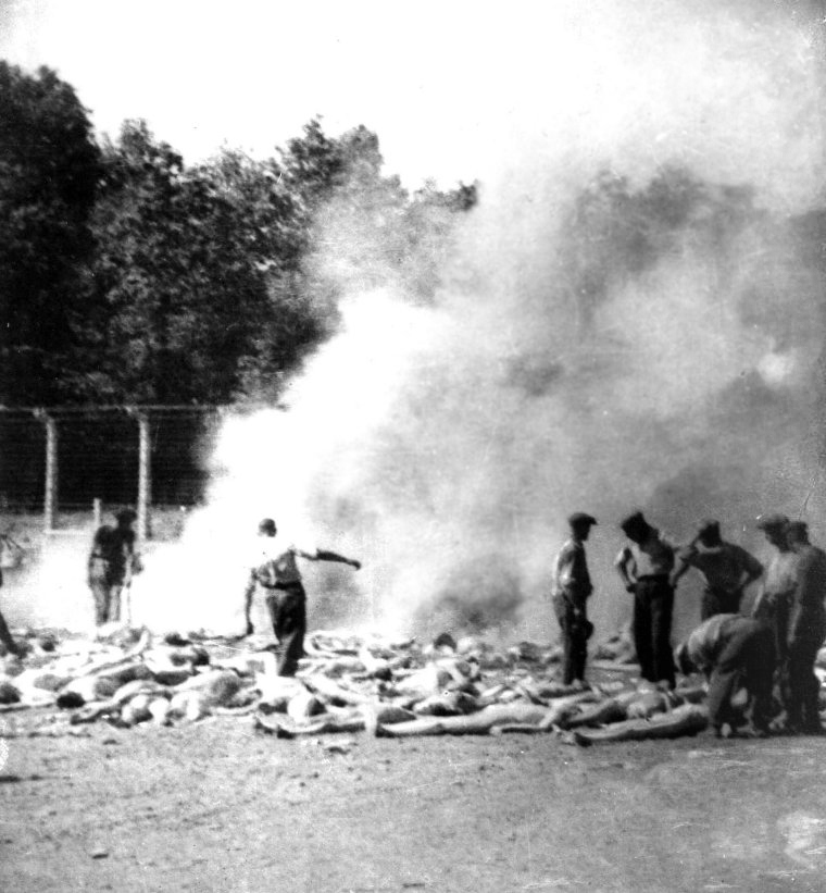 A row of corpses on the floor. Around the Sonderkommando inspect them next to a column of smoke