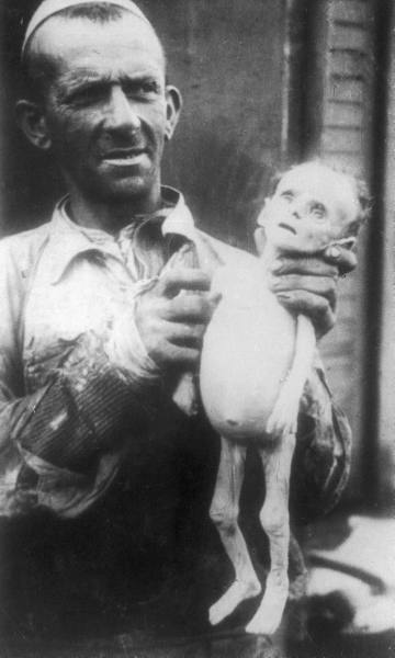 A man hols the corpse of a baby. It's thin like a skeleton and almost looks like a frightful doll