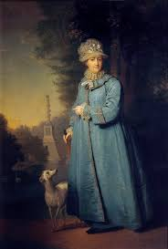 Catherine dressed casually in a blue coat and walks her dog in the gardens