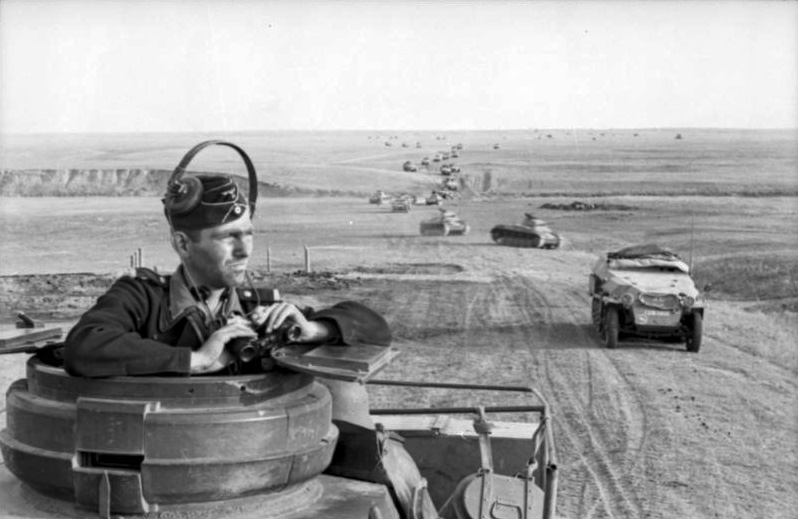 Panzer driver stares the horizon with binoculars on his hands. Behind him a column of Panzer advances in the steppe.
