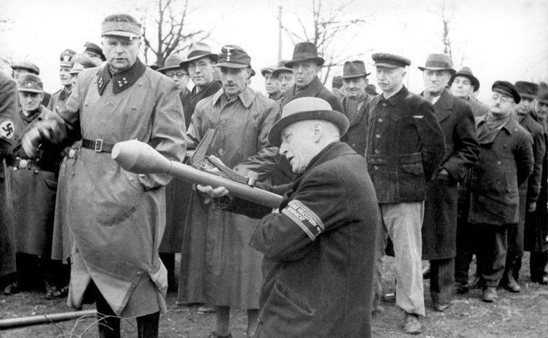 A middle-aged man aiming with the Panzerfaust while the soldier instructing watches