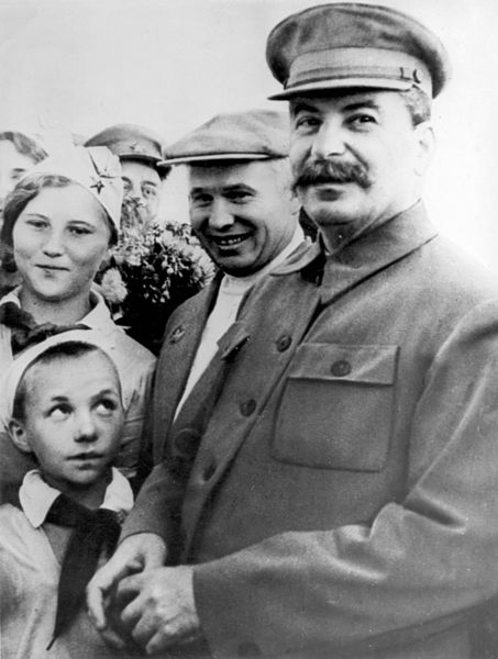 Stalin and Khrushchev smiling at the camera, they are surrounded by children and admirers.