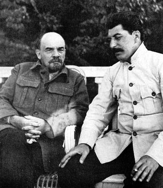 Lenin reclined talks to a listening Stalin who smiles gently