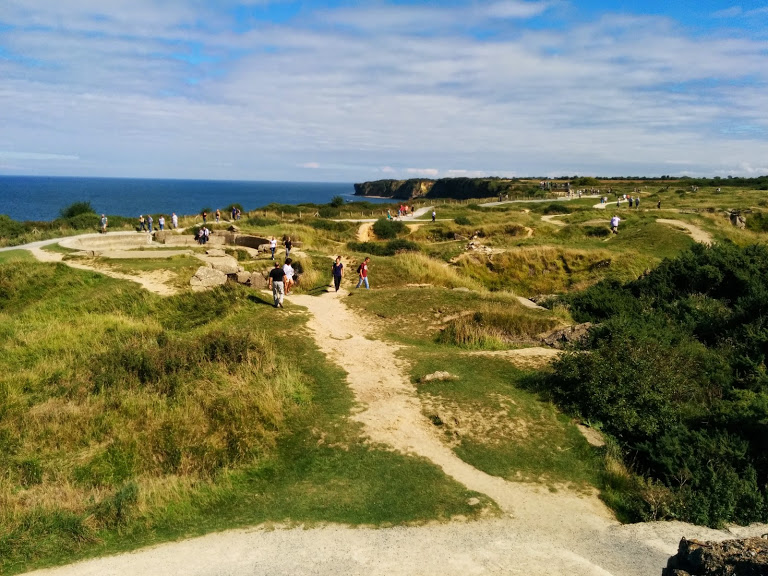 Path going through the demolished bunkers and craters of Pointe du Hoc. The edge of the cliff on the left hand side