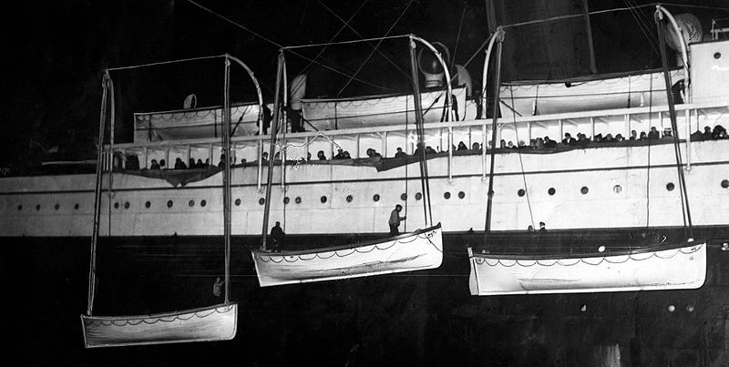 Passengers and survivors stare the Titanic's boats being loaded in the RMS Carpathia