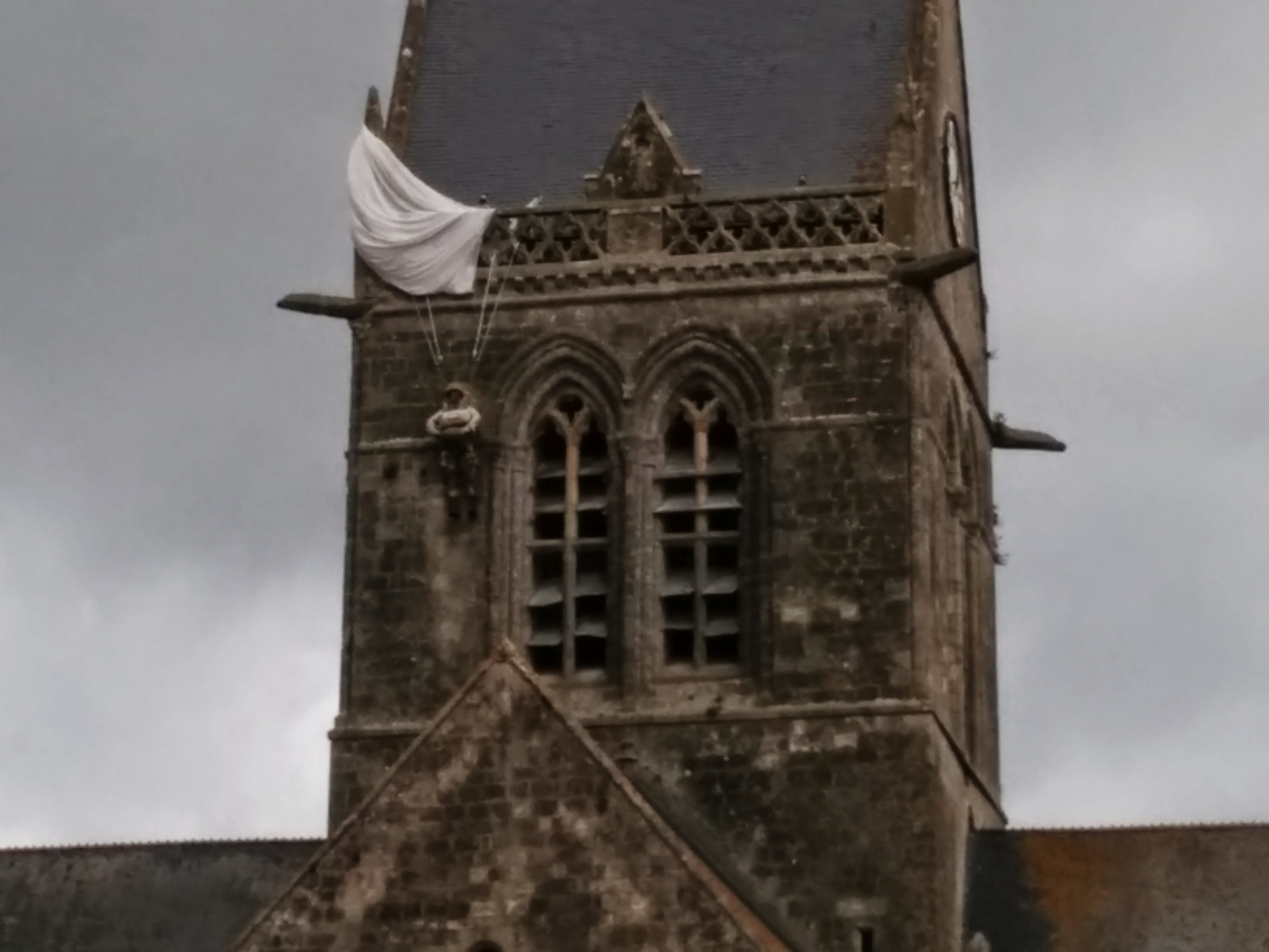 John Steele, a paratrooper of the 82nd Airborne, was stuck in the steeple of Sainte-Mère-'Église for two hours. He survived the war. Nowadays a dummy hanging in the church commemorates his story and the liberation of the town. Picture taken by me