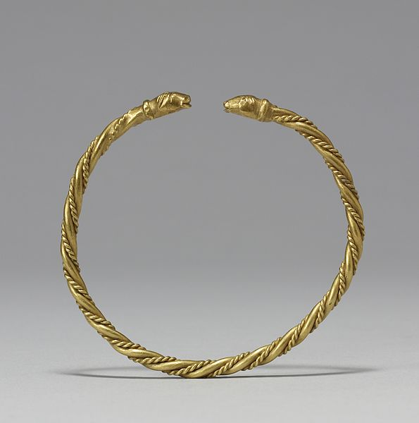 Golden arm ring with two worn-out heads shaped at each end.