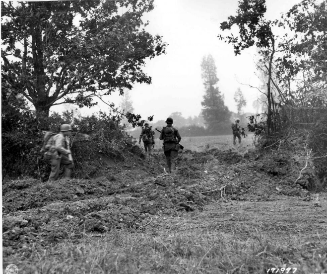 US Soldiers advance through a hole in the bocage made by a bulldozer