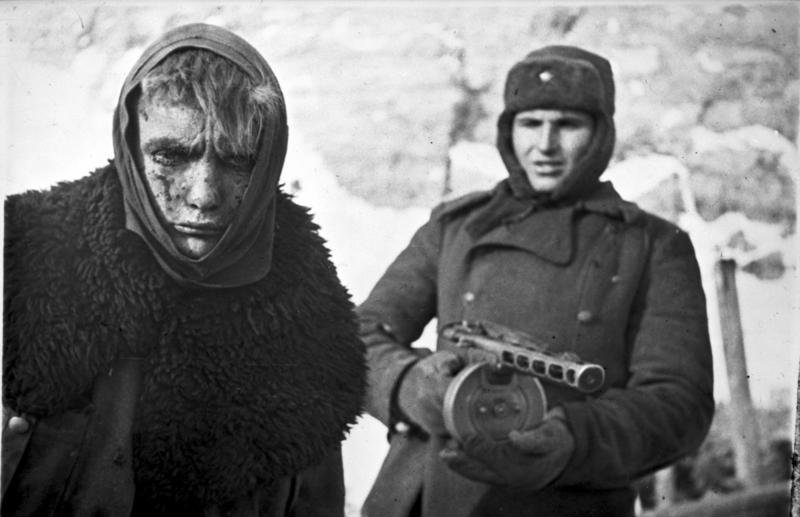 Battered and bleeding German prisoner escorted by a proud Soviet soldier