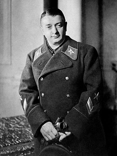 Tukhachevsky in his uniform, holds a cap and gloves on his hands