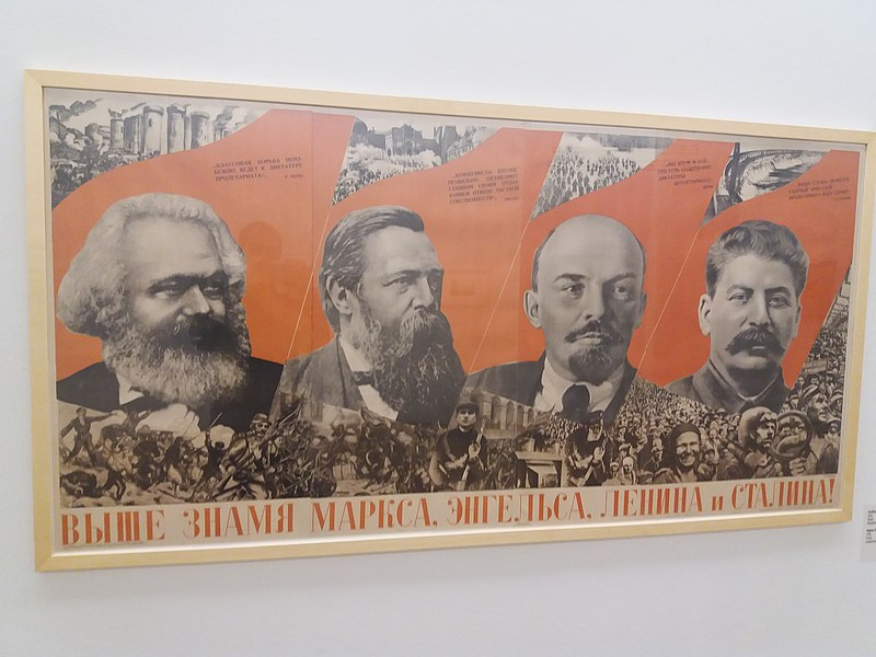 Poster with Marx, Engels, Lenin and Stalin faces, behind red banner, underneath pictures of people and crowds