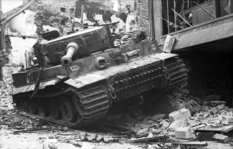 The Tiger seems intact, and is resting next to a destroyed building