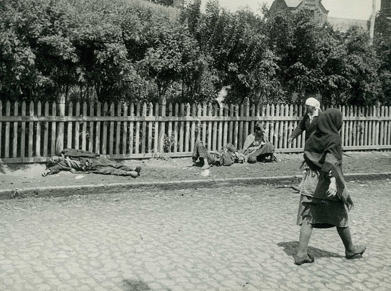 Two women walk past three peasants lying on the street, too weak to move. One of them might be dead