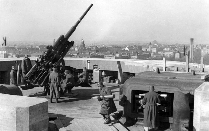 A flak gun on the Flak tower's roof while the men carry ammunition up and down