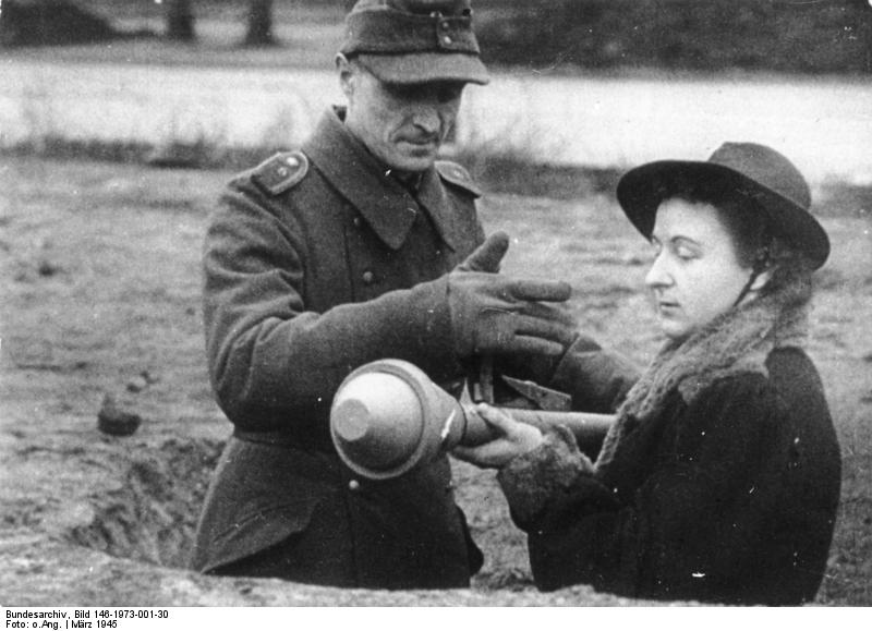 A soldier instructing a woman on how to shoot the Panzerfaust